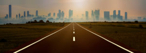 photograph of a highway leading into a city far off in the horizon.
