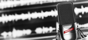 Image is of a studio microphone used in radio broadcasting in front of a screen showing audio wave files