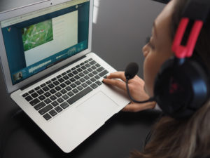 Woman sitting in front of her laptop reading aloud and recording her voice on VocaliD's Human Voicebank website