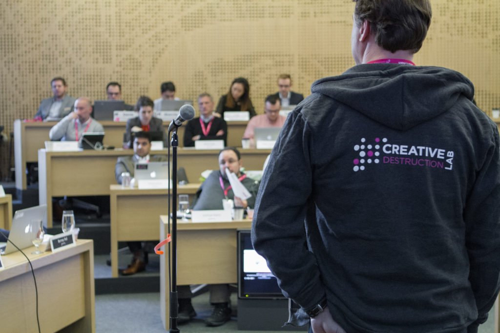 A program leader stands with his back to the camera while beyond him sits a small auditorium of students